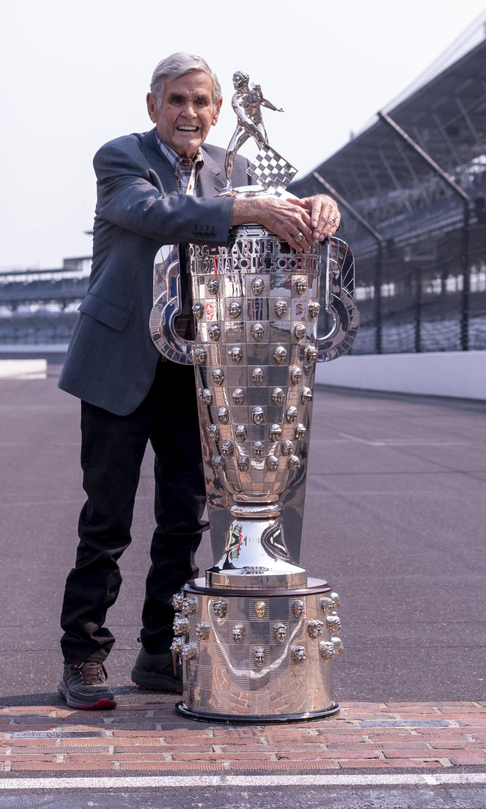 Retired race car driver Al Unser hugs the Borg-Warner Trophy while waiting for other four-time winners of the Indianapolis 500 auto race to arrive for a photo session at the Indianapolis Motor Speedway in Indianapolis, Tuesday, July 20, 2021. Winner of this year's Indy 500, Helio Castroneves, gathered with four-time winners - A.J. Foyt (1961, 1964, 1967, 1977), Unser (1970, 1971, 1978, 1987) and Rick Mears (1979, 1984, 1988, 1991) at the track. Castroneves won the race in 2001, 2002, 2009 and 2021. (AP Photo/Doug McSchooler)