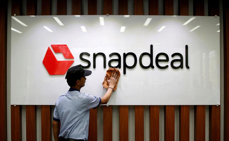 FILE PHOTO: An employee cleans a Snapdeal logo at its headquarters in Gurugram