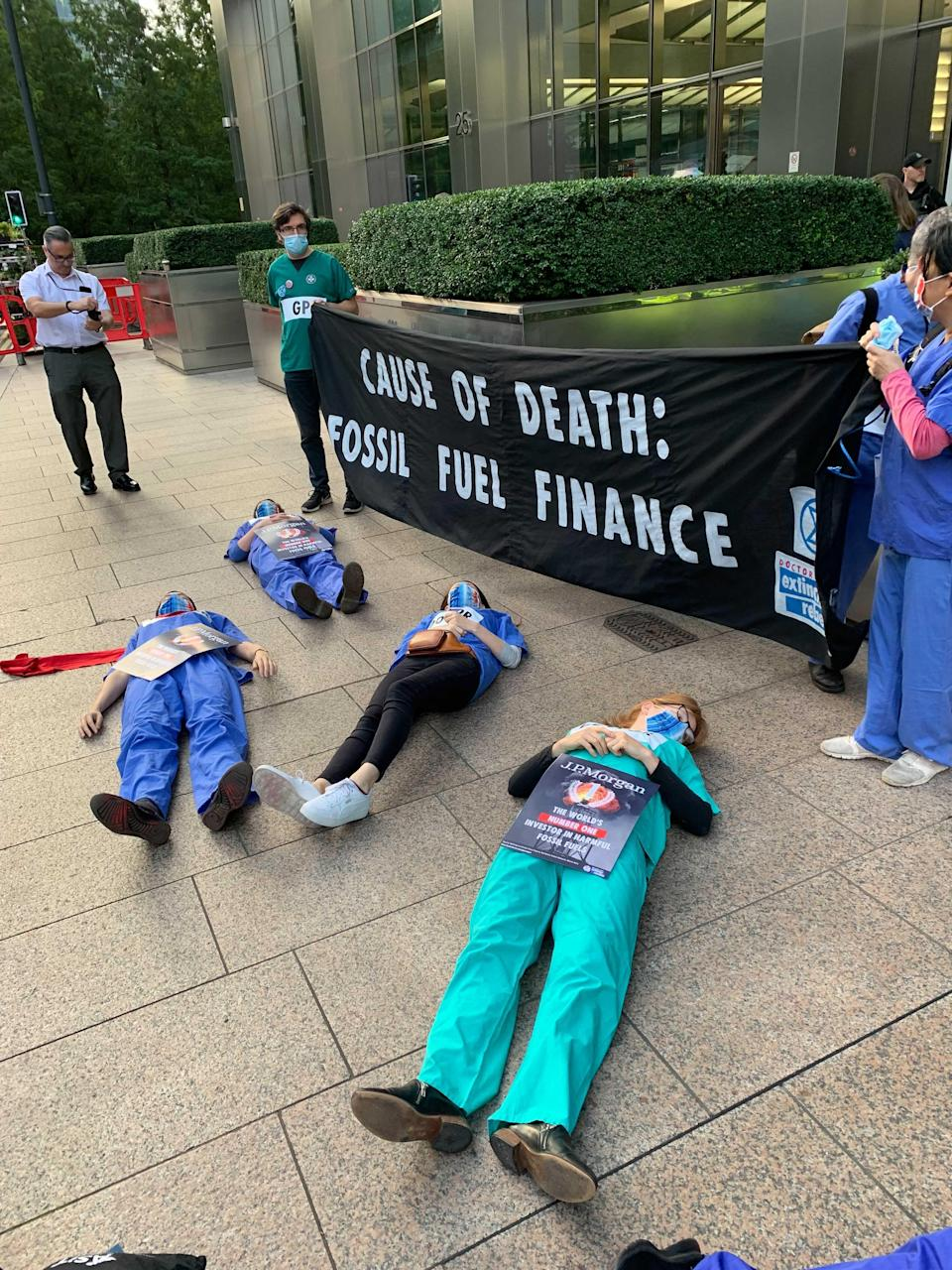 Protesters dressed in their scrubs lay on the floor and held banners in Canary Wharf (The Independent)