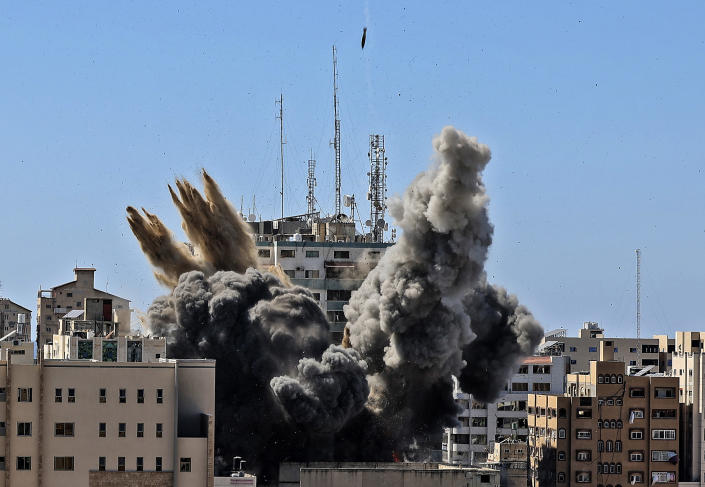 FILE - In this Saturday, May 15, 2021, file photo, an air bomb hits the building housing various international media, including The Associated Press, in Gaza City. Israel's defense minister has distanced himself from comments made by his military chief after Israel bombed the Gaza Strip high-rise housing an Associated Press office and other news outlets. (Mahmud Hams /Pool Photo via AP, File)