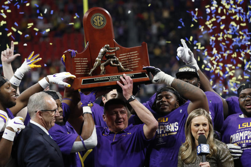 LSU head coach Ed Orgeron and team members celebrate with teammates after the Southeastern Conference championship NCAA college football game against Georgia, Saturday, Dec. 7, 2019, in Atlanta. LSU won 37-10. (AP Photo/John Bazemore)