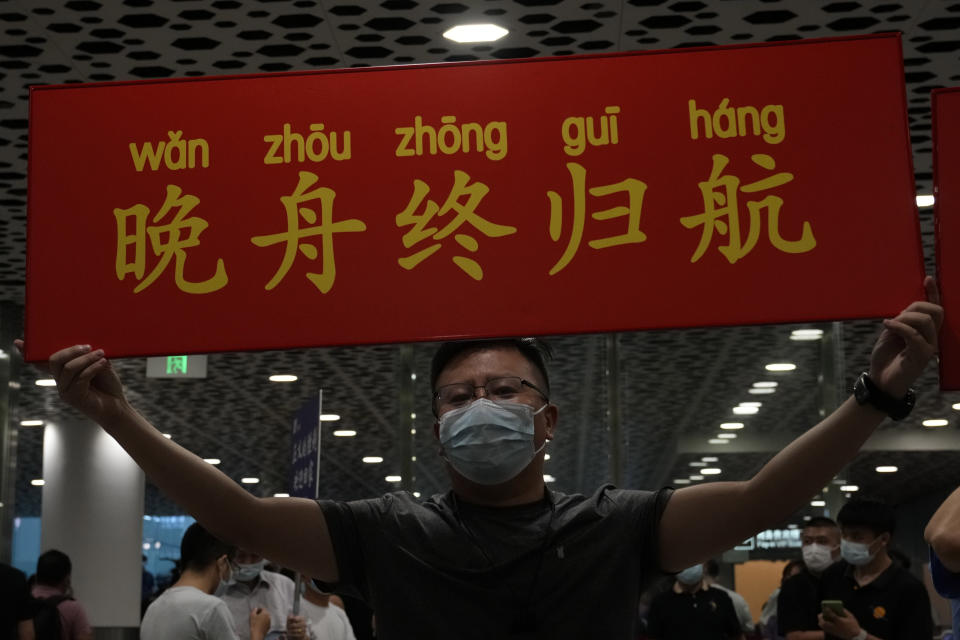 """A supporter of Huawei CFO Meng Wanzhou holds up a sign that reads """"Wan Zhou Finally Returns """"at the Shenzhen Bao'an International Airport in Shenzhen in southern China's Guangdong Province, Saturday, Sept. 25, 2021. A top executive from global communications giant Huawei Technologies returned to China on Saturday following what amounted to a high-stakes prisoner swap with Canada and the U.S. (AP Photo/Ng Han Guan)"""