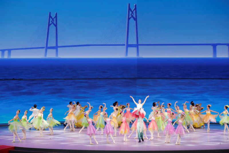 Performers take part in a cultural performance with an image of the Hong Kong-Zhuhai-Macau bridge seen in the background in Macau
