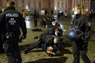 Police arrest a man at Bebelplatz square after they tried to disperse a crowd of revellers following celebrations at the Brandenburg Gate in Berlin, early on January 1, 2021