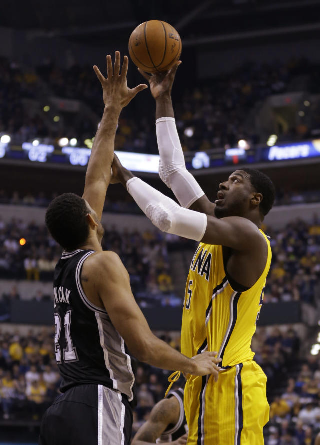 Indiana Pacers center Roy Hibbert, right, shoots over San Antonio Spurs forward Tim Duncan in the first half of an NBA basketball game in Indianapolis, Monday, March 31, 2014. (AP Photo/Michael Conroy)