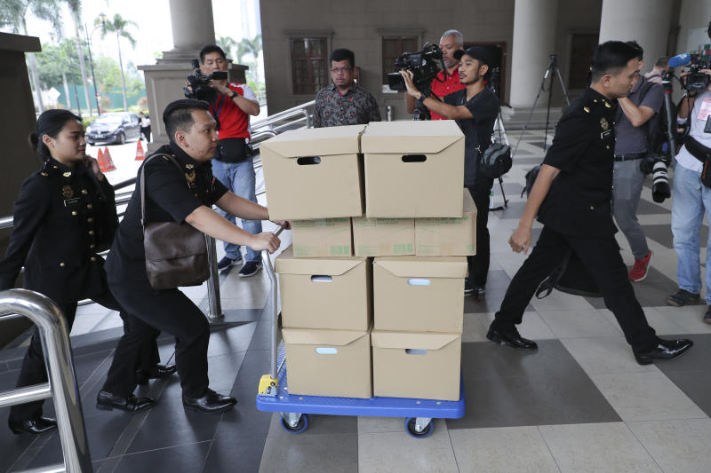 FILE - In this Wednesday, Aug. 28, 2019, file photo, Malaysian Anti-Corruption agency's staff transport documents for 1MDB case to Kuala Lumpur high court in Kuala Lumpur, Malaysia. Malaysia has ordered 80 people and groups to pay fines totaling about $100 million for allegedly receiving funds from the 1MDB state investment fund. Najib faces 42 charges of corruption, abuse of power and money laundering in five separate criminal cases linked to the multibillion-dollar looting of 1MDB.  (AP Photo/Vincent Thian, File)