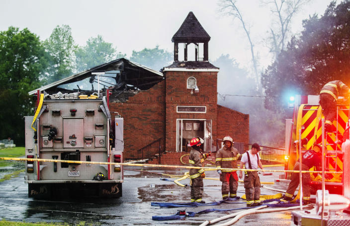 FILE - In this April 4, 2019, file photo, firefighters and fire investigators respond to a fire at Mount Pleasant Baptist Church, in Opelousas, La. Vice President Mike Pence is coming to Louisiana to show his support for members of three black churches, including Mount Pleasant, burned by an arsonist. (Leslie Westbrook/The Advocate via AP, File)