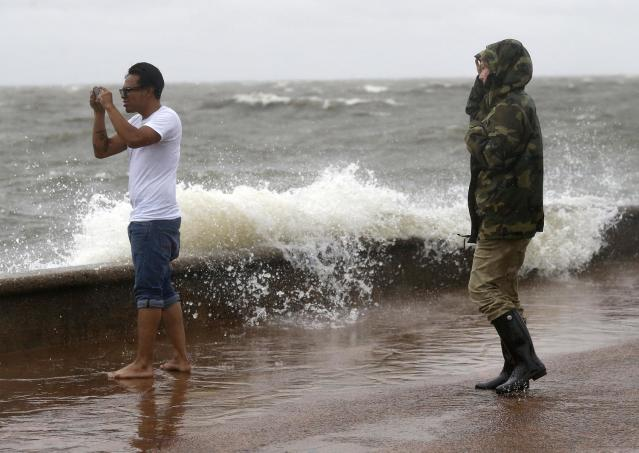 <p>Julie Plaisance, right, and Renee Davila take photos on the shore of Lake Pontchartrain as weather from Tropical Storm Cindy, in the Gulf of Mexico, impacts the region in New Orleans, June 20, 2017. (Photo: Gerald Herbert/AP) </p>