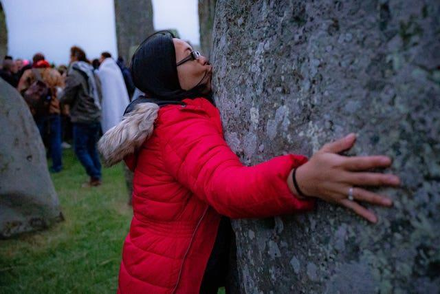 A woman kisses a stone during Summer Solstice