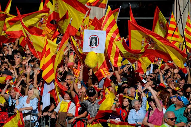 "<p>A demonstrator holds a placard bearing a crossed-out portrait of Catalan regional leader Carles Puigdemont, who was officially ousted by Madrid, reading ""Dictators out"" as others wave Spanish and Catalan Senyera flags during a pro-unity demonstration in Barcelona on Oct. 29, 2017. (Photo: Lluis Gene/AFP/Getty Images) </p>"