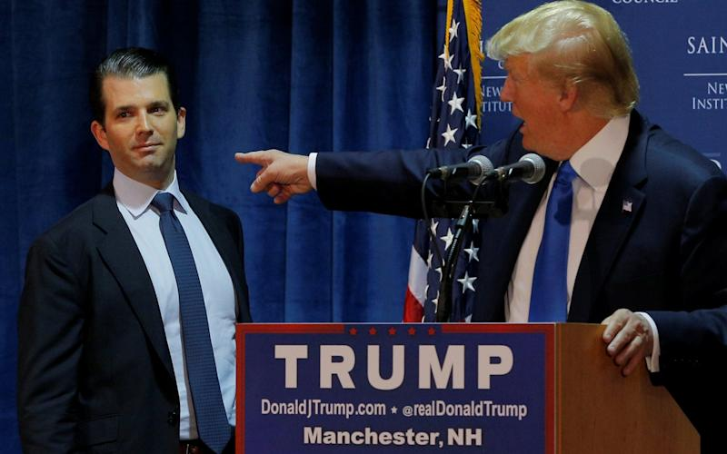 Then Republican presidential candidate Donald Trump welcomes his son Don Jr. to the stage at a November 2015 event in Manchester,New Hampshire - REUTERS