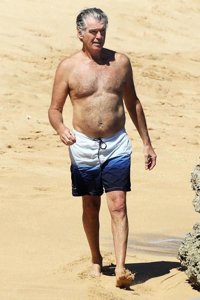 <p>Pierce Brosnan enjoys a walk on the beach while in Hawaii with his family on Friday.</p>