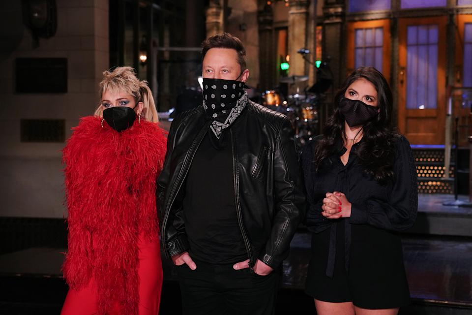 (L-R): Miley Cyrus, Elon Musk, and Cecily Strong depicted in a promo for Saturday Night Live. (Photo:  Rosalind O'Connor/NBC/NBCU Photo Bank via Getty Images)