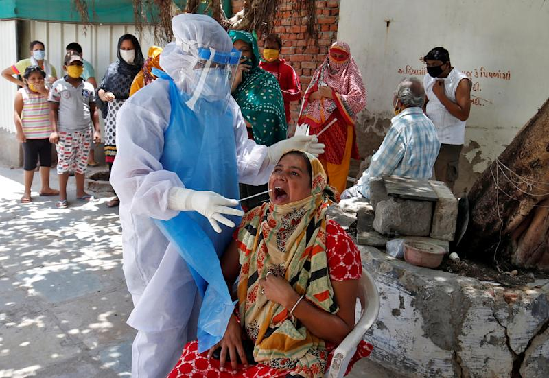 A woman reacts as a healthcare worker wearing a protective gear takes a swab to test for the coronavirus disease (COVID-19) at a residential area in Ahmedabad, India, May 22, 2020. REUTERS/Amit Dave??
