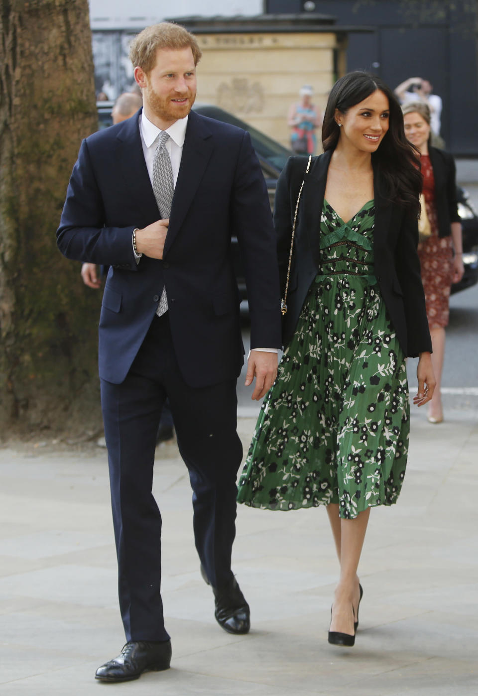 """<p>Royal watchers will notice that Markle opted not to drape her blazer over her shoulders this time — something that was slammed as """"unprofessional"""" and against royal protocol when she did it earlier this week. <br>Markle also took two style cues from Kate Middleton. First of all, she wore Alexander McQueen (the Duchess of Cambridge is a major fan — she's been spotted wearing countess McQueen creations, including her wedding dress). Secondly, she showed that like Kate, she's a fan of rewearing her favourite looks. Markle was spotted wearing the same blazer, this time combined with pants, at her first official appearance with Prince Harry back in February. </p>"""