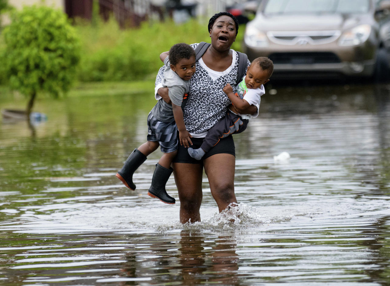 Terrian Jones reacts as she feels something moving in the water at her feet as she carries Drew and Chance Furlough to their mother on Belfast Street near Eagle Street in New Orleans after flooding from a 100-year storm from a tropical wave system in the Gulf Mexico dumped lots of rain in Wednesday, July 10, 2019. The wave system may form into a hurricane called Barry later in the week. (AP Photo/Matthew Hinton)