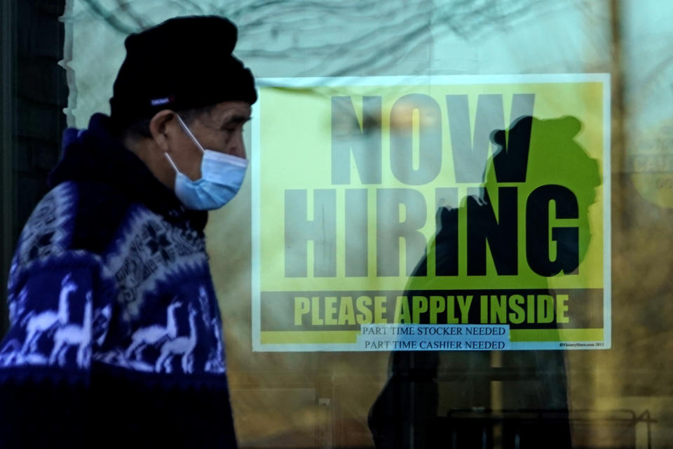 A shopper wears a face mask and he walks past a store displaying a hiring sign in Wheeling, Ill., Saturday, Nov. 28, 2020. More than 65,000 unemployment claims were filed statewide last week due to COVID-19 in Illinois. (AP Photo/Nam Y. Huh)