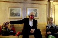 In this photo provided by the Albanian Prime Minister's office, Albania's Prime Minister Edi Rama sits at a hotel in Beirut, Lebanon, Monday, 26, 2020, with Albanian children as part of an operation to take them back home to Albania from Al Hawl, northern Syria. A few hundred Albanian men are known to have joined terror groups in Syria and Iraq in the early 2010s, and now many of them are dead and their family members are stuck in Syria camps, but will be repatriated via Beirut to Albania. (Albanian Prime Minister's office via AP)