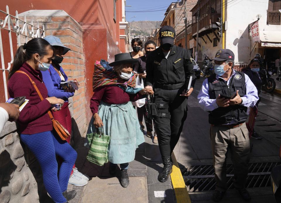 Indigenous woman Maria Cajavilca, 83, is escorted by a police officer in Huamanga, Peru, Thursday, Sept. 2, 2021. Cajavilca, who speaks only Quechua, was found lost, not remembering where she lives, and the police officer was one of the few people who understood her and could help. (AP Photo/Martin Mejia)