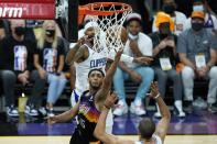 Phoenix Suns guard Cameron Payne (15) scores against Los Angeles Clippers forwards Nicolas Batum, right, and Marcus Morris Sr., back left, during the first half of Game 1 of the NBA basketball Western Conference finals Sunday, June 20, 2021, in Phoenix. (AP Photo/Ross D. Franklin)
