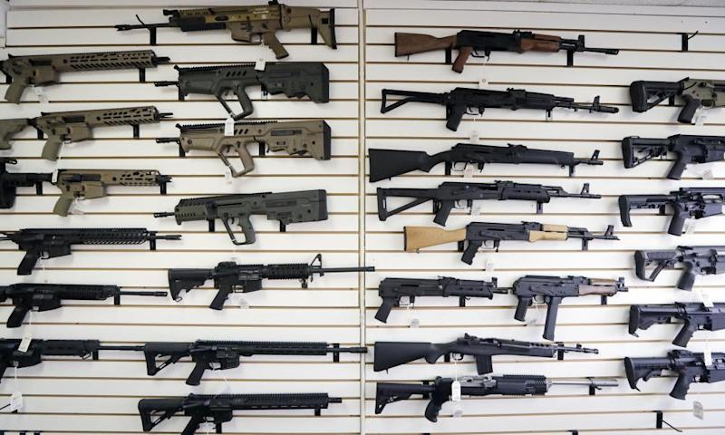Semi-automatic rifles fill a wall at a gun shop in Lynnwood, Washington, in 2018. As of 1 January, no one under the age of 21 in Washington can purchase a such weapons.