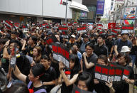 """Protesters carrying signs reading """"Demand accountability for shooting/Withdraw charges!"""" march through the streets against an extradition bill on Sunday, June 16, 2019, in Hong Kong. Tens of thousands of Hong Kong residents, mostly in black, have jammed the city's streets Sunday to protest the government's handling of a proposed extradition bill. (AP Photo/Vincent Yu)"""