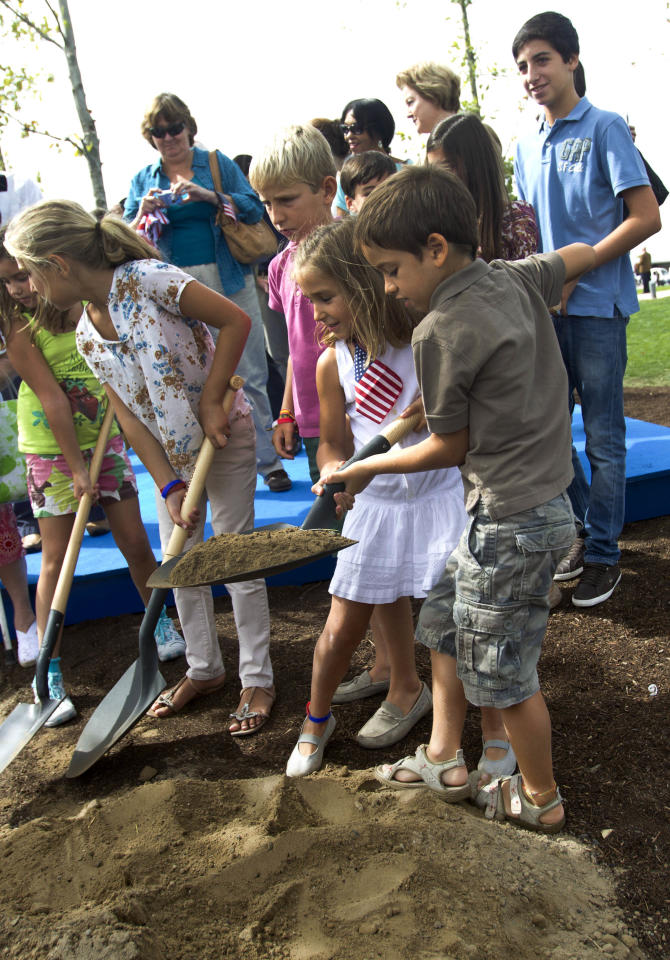 Children help plant a tree during a commemorative ceremony in Madrid Sunday Sept. 11, 2011 to mark the tenth anniversary of the terrorist attacks in New York, Washington D.C. and Pennsylvania.  (AP Photo/Paul White)
