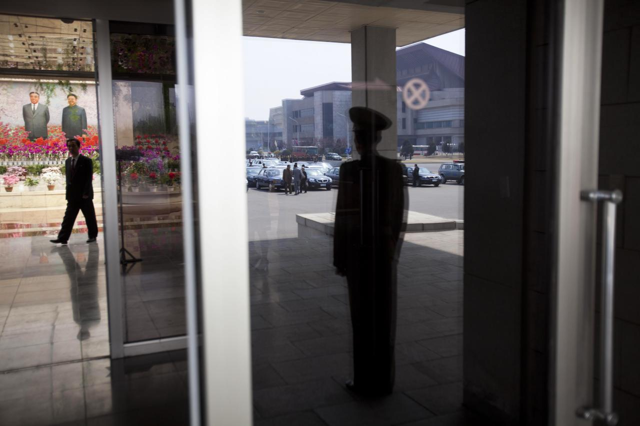 In this April 13, 2011 photo, a guard reflected in a window stands by the entrance to a hall where organizers held an exhibition of the flowers known in North Korea as Kimjongilia and Kimilsungia, in Pyongyang, North Korea. (AP Photo/David Guttenfelder)