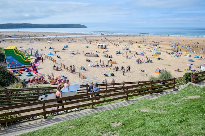 Surfers and sunseekers flock to the beach at Woolacombe, on the North Devonshire coast following the hottest August Bank Holiday Monday on record, with temperatures reaching 33.2C. The heatwave is set to continue for some parts of the UK after the record-breaking bank holiday weather. (Photo by Ben Birchall/PA Images via Getty Images)