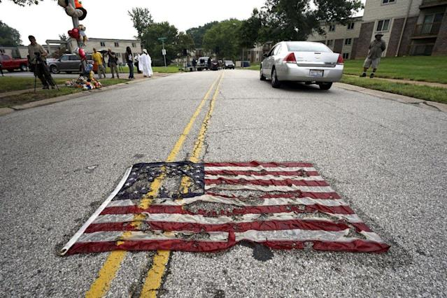 <p>A partially burned American flag lies on the street near the spot where Michael Brown was killed before an event to mark the one-year anniversary of the his death in Ferguson, Missouri August 9, 2015. (Rick Wilking/Reuters) </p>