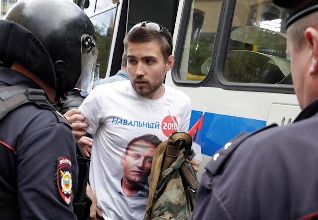 <p>Riot police detain a man dressed in a t-shirt depicting opposition leader Alexei Navalny, during the Navalny-led anti-corruption protest in central Moscow, Russia, June 12, 2017. (Maxim Shemetov/Reuters) </p>