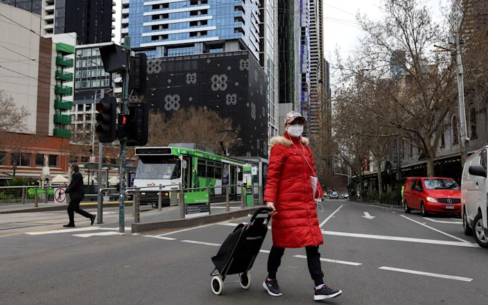 A woman wearing a face mask crosses a street in Melbourne, Victoria, Australia, 06 August 2021. Victoria has entered a seven-day lockdown in an effort to contain a growing outbreak of the COVID-19 Delta variant in the state. COVID-19 lockdown in Melbourne, Australia - Shutterstock