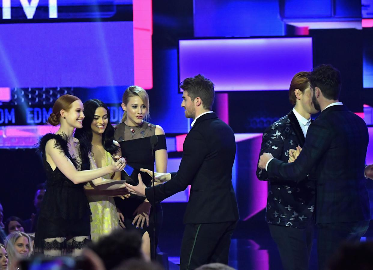 LOS ANGELES, CA - NOVEMBER 19: (L-R) Madelaine Petsch, Camila Mendes, Lili Reinhart, and (2nd from R) KJ Apa present Andrew Taggart (3rd from R) and Alex Pall (R) of The Chainsmokers with the Favorite Artist - Electronic Dance Music (EDM) award onstage during the 2017 American Music Awards at Microsoft Theater on November 19, 2017 in Los Angeles, California. (Photo by Lester Cohen/WireImage)