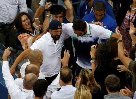 Marin Cilic of Croatia (center, R) goes into the stands to embrace his coach Goran Ivanisevic after defeating Kei Nishikori of Japan during their men's singles final match at the 2014 U.S. Open tennis tournament in New York, September 8, 2014.      REUTERS/Shannon Stapleton
