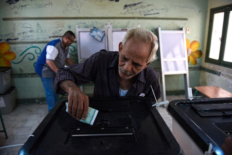 A man casts his ballot in the Egyptian parliamentary elections at a polling station in the Giza district of the capital Cairo, on October 18, 2015 (AFP Photo/Mohamed El-Shahed)