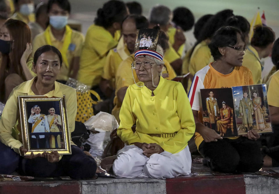 Supporters of the monarchy hold images of Thailand's King Maha Vajiralongkorn and Queen Suthida, as they wait to see their motorcade near Thammasat University in Bangkok, Thailand, Saturday, Oct. 31, 2020. officiating a graduation ceremony at Thammasat University in Bangkok, Thailand, Saturday, Oct. 31, 2020. Thailand's king has presided over a university graduation ceremony at a stronghold of a protest movement seeking to reduce the monarchy's powers, after activists issued a call for students to boycott the event. (AP Photo/Sunti Teapia)