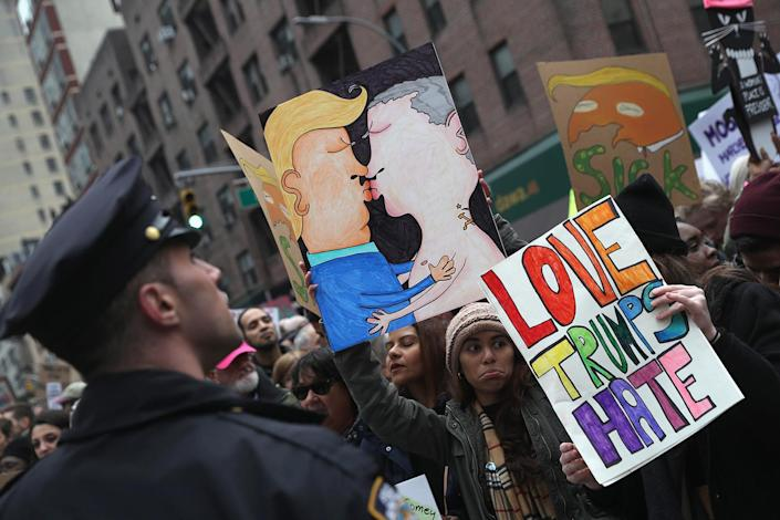 <p>People hold up a drawing of Donald Trump and Vladimir Putin kissing while taking of part in the Women's March on January 21, 2017 in New York City. (John Moore/Getty Images) </p>