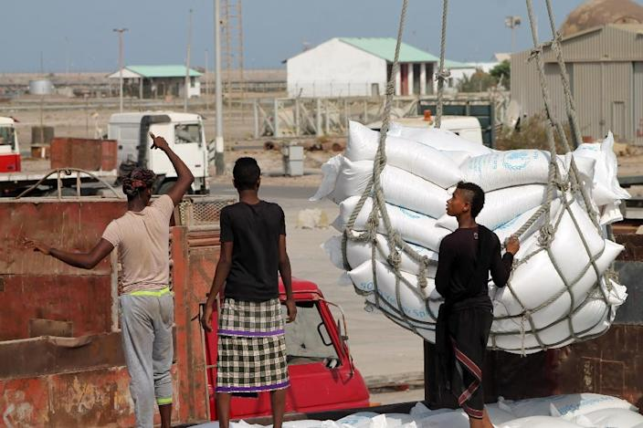 Workers unload bags from a UN World Food Programme ship docked in Yemen's devastated port city of Aden (AFP Photo/)
