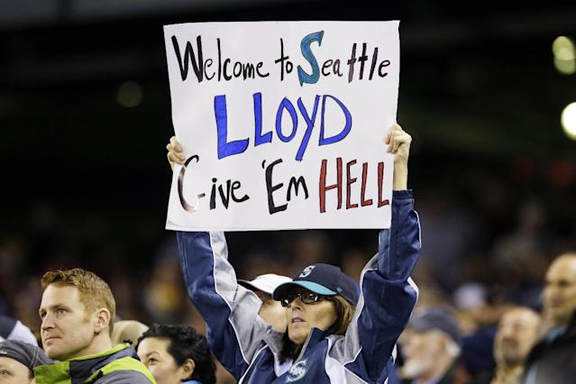 A fan holds a sign supporting new Seattle Mariners manager Lloyd McClendon during the Mariners' baseball game against the Los Angeles Angels, Tuesday, April 8, 2014, in Seattle. (AP Photo/Ted S. Warren)