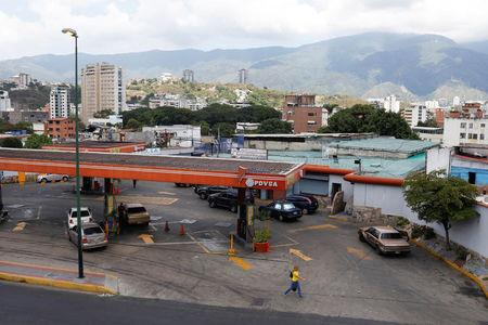 Pedestrians walk next to a gas station of Venezuelan state-owned oil company PDVSA in Caracas