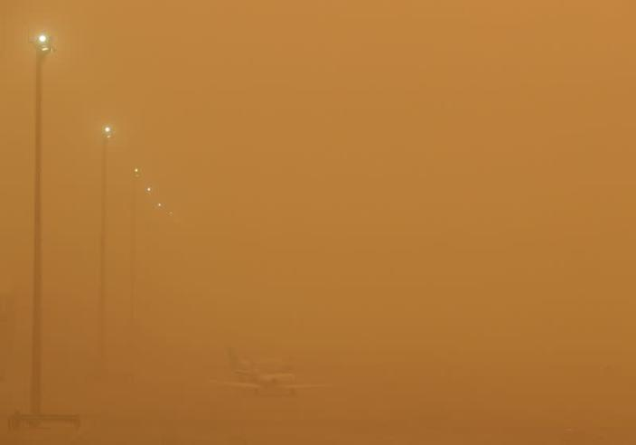 """Planes are seen parked on the tarmac during a sandstorm blown over from North Africa known as """"calima"""" at Las Palmas Airport"""