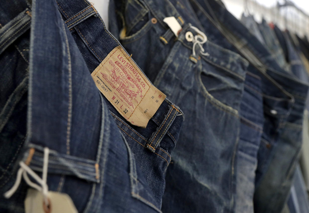 FILE- This Feb. 9, 2018 photo shows Levi's jeans hanging on a wall at Levi's innovation lab in San Francisco. Well-known jeans company Levi Strauss & Co. said Wednesday, Feb. 13, 2019, that it plans to raise about $100 million through an initial public offering. The number of shares to be offered and the price range has yet to be determined. (AP Photo/Jeff Chiu, File)