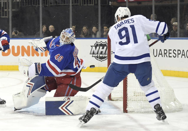New York Rangers goaltender Alexandar Georgiev (40) eyes the puck as Toronto Maple Leafs center John Tavares (91) attempts to get his stick on the puck during the first period of an NHL hockey game Sunday, Feb. 10, 2019, at Madison Square Garden in New York. (AP Photo/ Bill Kostroun)