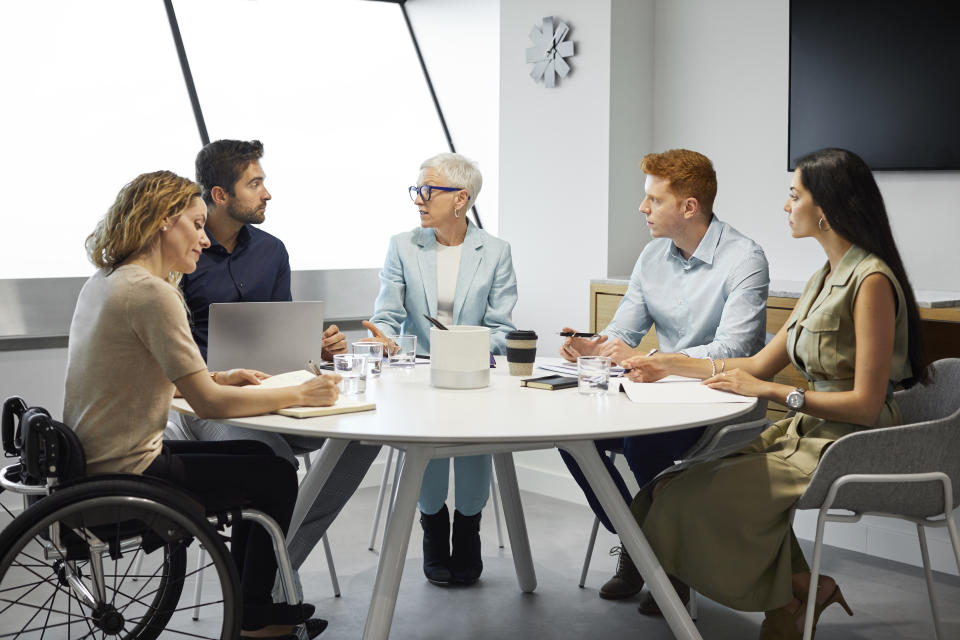 Male and female colleagues planning strategy in meeting. Business professionals discussing around conference table. They are in board room at office.