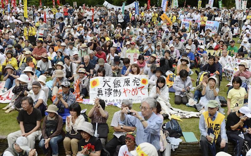 """In this June 17, 2012 photo, people gather for a rally in Fukui city to protest against the restart of two nuclear reactors in Ohi town, Fukui prefecture, western Japan. Public opposition to resuming operations remains high, however, because of the March 2011 crisis at Fukushima Dai-ichi plant that turned into the world's worst atomic disaster since Chernobyl and a lingering distrust of an industry widely seen as opaque. The banner reads: Please stop reactivating the Ohi nuclear plant."""" (AP Photo/Kyodo News) JAPAN OUT, MANDATORY CREDIT, NO LICENSING IN CHINA, HONG KONG, JAPAN, SOUTH KOREA AND FRANCE"""