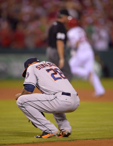 Houston Astros first baseman Jon Singleton, below, squats down as Los Angeles Angels' C.J. Cron round second after hitting a three-run home run during the seventh inning of a baseball game, Saturday, July 5, 2014, in, Anaheim, Calif. (AP Photo/Mark J. Terrill)