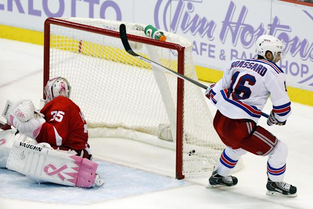New York Rangers center Derick Brassard (16) scores the winning goal on Detroit Red Wings goalie Jimmy Howard during the first overtime period of an NHL hockey game Saturday, Oct. 26, 2013, in Detroit. The Rangers won 3-2. (AP Photo/Duane Burleson)