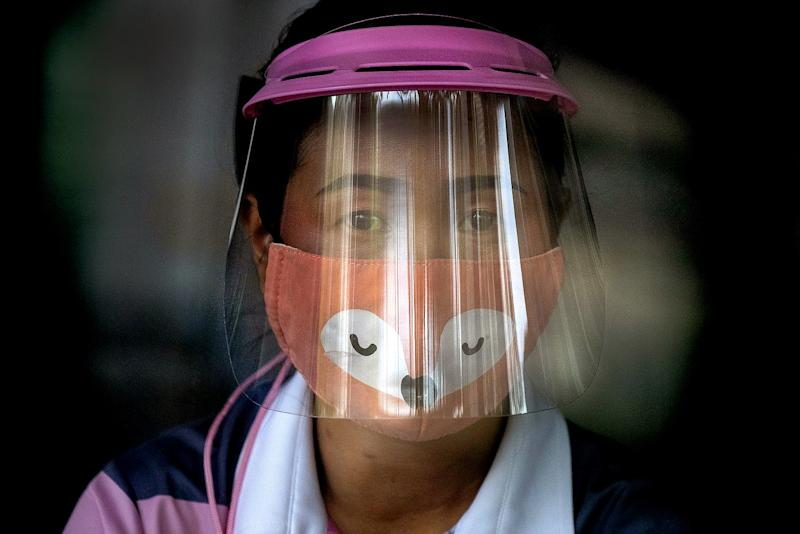 THAILAND: A volunteer at a COVID-19 screening center in Bangkok wears a face mask and a face shield.