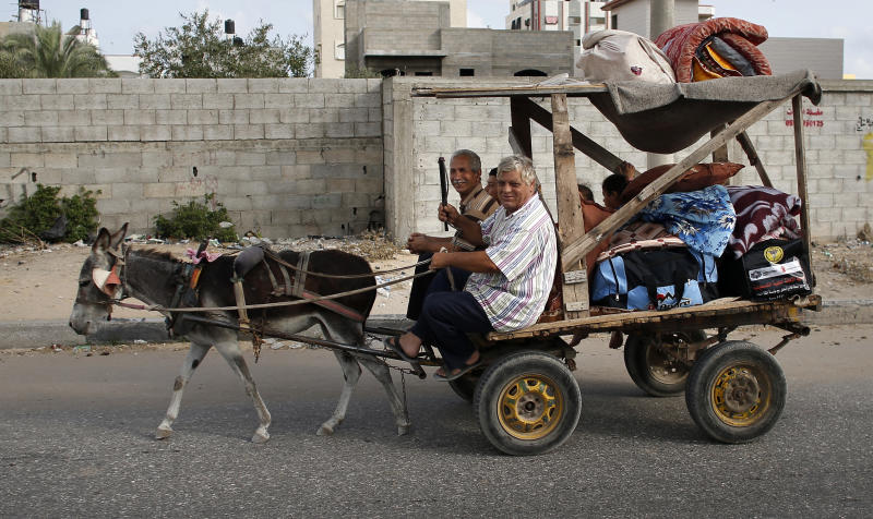 Palestinian families travel to a UN school in Gaza City to seek shelter after evacuating their homes on July 13, 2014