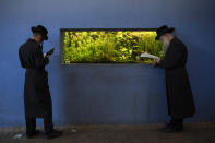 Ultra-Orthodox Jews pray during the Tashlich ceremony, next to an aquarium at a zoo in the ultra-Orthodox Israeli town of Bnei Brak, Tuesday, Sept. 14, 2021. Tashlich, which means 'to cast away' in Hebrew, is the practice by which Jews go to a large flowing body of water and symbolically 'throw away' their sins by throwing a piece of bread, or similar food, into the water before the Jewish holiday of Yom Kippur, the holiest day in the Jewish year which starts at sundown Wednesday. (AP Photo/Oded Balilty)